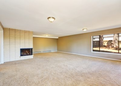 Empty beige room with fireplace and carpet floor.